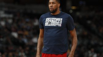 Derrick Favors standing in front of a crowd